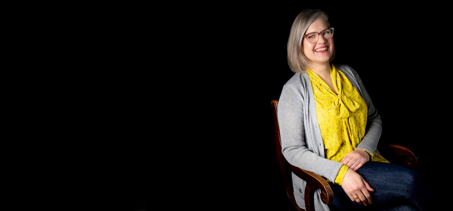 Photo of the therapist on a black background. She is seated in an armchair that is turned 45 degrees to the left, and she is leaning toward the right, with her right arm resting on the right arm of the chair. The picture is cropped to show her from the lap up. She is a middle-aged White woman in partial profile, smiling and looking toward the viewer. She has medium length blonde and grey hair, and blue eyes. She is wearing pink eyeglasses, dark blue jeans, a bright yellow blouse, and a light grey cardigan sweater.