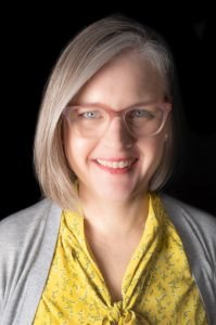 Photo of Amy's head and shoulders. She is a middle-aged White woman, facing the viewer and smiling. She has medium length blonde and grey hair, and blue eyes. She is wearing pink eyeglasses, a bright yellow blouse, and a grey cardigan sweater.